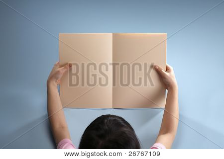 Stock image of a girl holding a blank book.