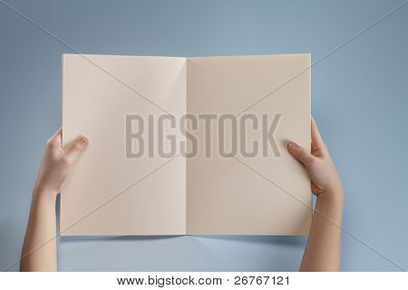 Human hands holding a book.