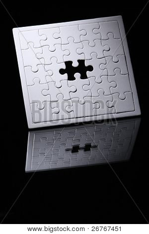 Jigsaw puzzle with missing piece isolated on black background.