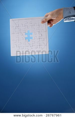 Human hand holding an incomplete jigsaw puzzle.