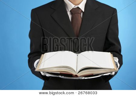 A man handing out a book on a tray.