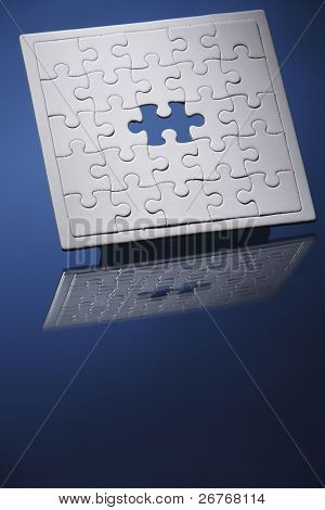 Jigsaw puzzle with missing piece isolated on blue background.