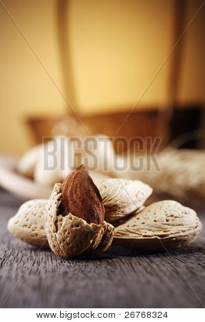 Almonds with wooden spoon and wheat.