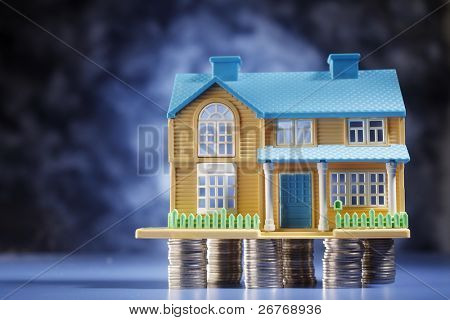 A model house on a few stacks of coins.