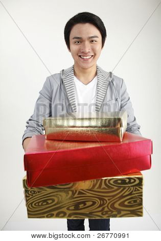 Young man carrying stack of gifts, smiling, portrait
