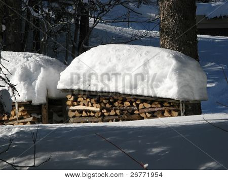 Pile of firewood covered by fresh snow