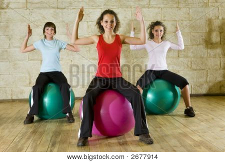 Young Women Working Out Siting On Big Balls