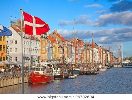 COPENHAGEN, DENMARK - AUGUST 25: unidentified people enjoy sunny weather in open cafees of the famous Nyhavn promenade on August 25, 2010 in Copenhagen, Denmark
