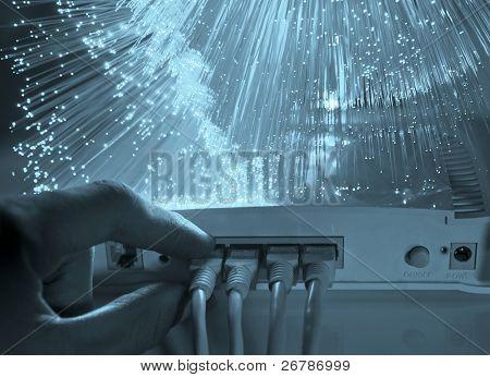 mão de pessoas com rede cabo e hub closeup com fundo óptico de fibra