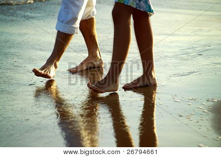 close up shot of a couple walking at the beach