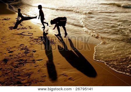 Silhouetted mother and kids playing at the beach