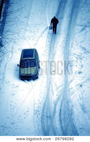 elevated view of man walking snow covered ground and parked car