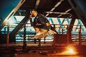 Young cool man break dancer jumping. Urban bridge with cool and warm lights background. poster