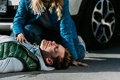 Cropped Shot Of Woman Checking Heartbeat Of Victim After Traffic Collision poster