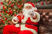 Santa Claus With Giftbox On Background Of Sparkling Firtree. Chr poster