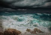 Stormy sea view  near coastline at evening time. Waves, splashed drops under dark dramatic sky. poster
