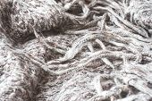 Crumpled Grey Knitted Scarf. Soft And Warm Fabric Is Crumpled Into Folds. Texture For Background Or  poster