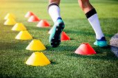 Football Player Jogging And Jump Between Cone Markers On Green Artificial Turf For Football Training poster