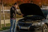 A Young Man Is Standing By A Broken Car And Looks Under The Car Hood.a Young Man Is Standing By  Bro poster