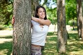 picture of teenage girl  - beautiful young woman in park playing peekaboo - JPG