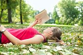 stock photo of reading book  - young woman relaxing and reading book - JPG