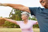 Senior woman stretching arms at park with her husband. Happy aged couple doing yoga exercise outdoor poster