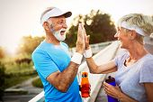 Beautiful Mature Couple Jogging In Nature Living Healthy poster