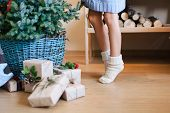 Little Child Girl Is Decorating Christmas Tree With Ornaments. Kid In Woolen Knitted Socks Stands On poster