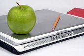 picture of students classroom  - Laptop computer with book pencil and green apple on white background - JPG