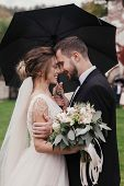 Gorgeous Bride And Stylish Groom Gently Hugging Under Umbrella In Rainy Outdoors. Sensual Wedding Co poster