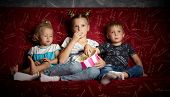 Childrens Movies: Three Children Watch Movies At Home On A Big Red Sofa In The Dark And Eat Popcorn. poster