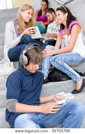 Students sitting on high-school stairs in break music reading teens