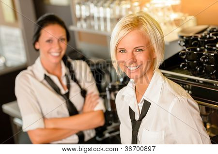 Cafe waitresses behind bar smiling at work break women colleagues