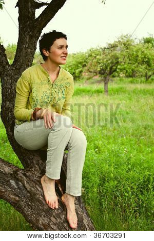 beautiful girl sitting on large tree in the garden