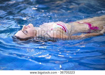 Young Girl Floating In The Outdoor Swimming Pool