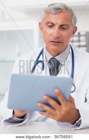 Médico usando um tablet PC em um consultório médico