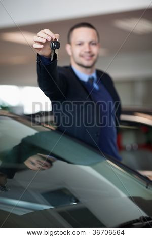 Salesman raising his arm while holding car keys in a dealership