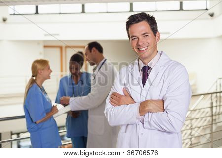 Doctor next to medical team in hospital corridor
