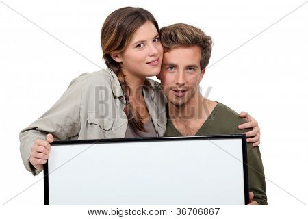 happy couple holding a blank poster