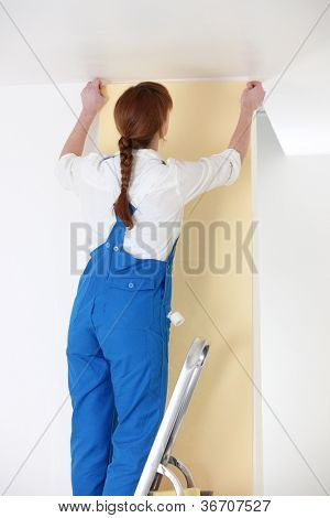 Woman putting up yellow wallpaper