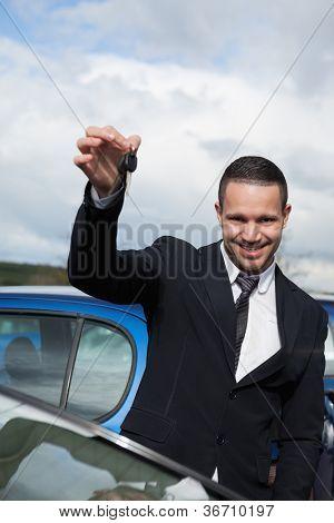 Happy man holding car keys outdoors