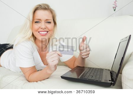 Woman lying with a thumb up and a credit card using a laptop