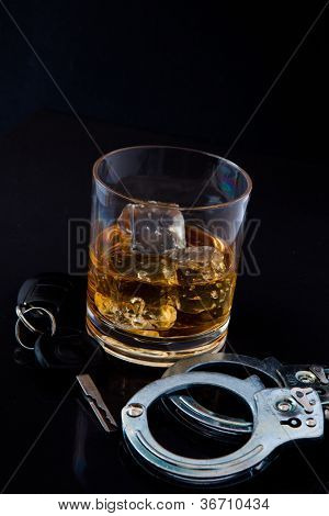 Whiskey on the rocks with car key and handcuff against a black background