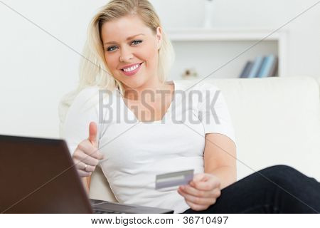 Woman with a credit and using a laptop on a sofa