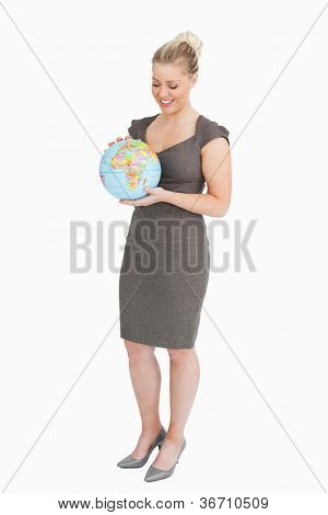 Businesswoman looking at globe in her hands against white background