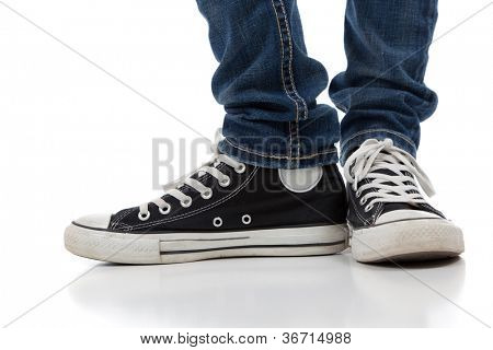 A pair of vintage looking, athletic shoes and skinny jeans on a white background with copy space