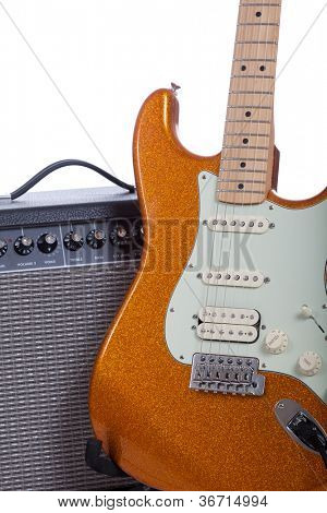 An orange electric guitar and amplifier