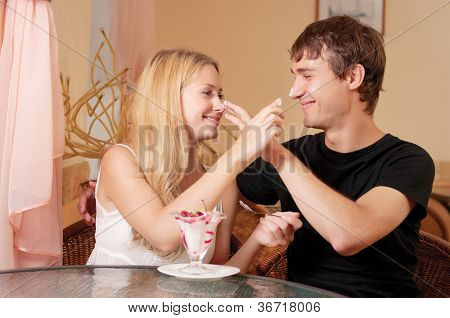 Young cople in cafe eat dessert