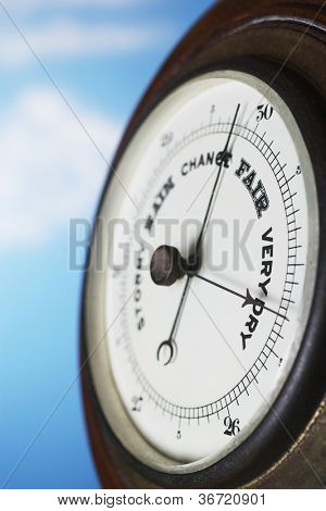 Closeup of weather barometer over blue background