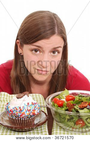 Muchacha con ensalada saludable y un cupcake